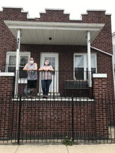 Two people standing on front porch.