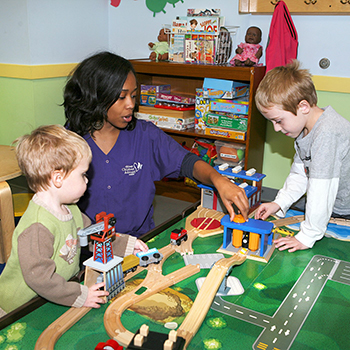 child care provider at activity table with children
